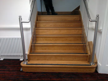 Stainless steel handrail system with steel balusters. Newels finished with stainless steel ball.